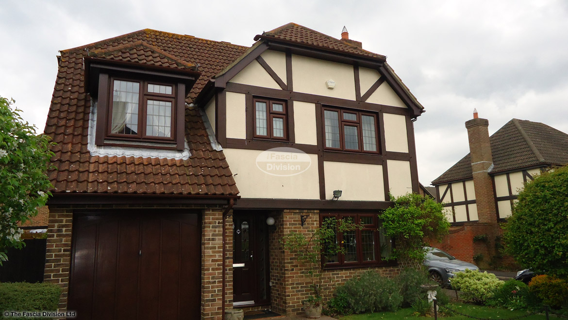 Installation of rosewood fascias and soffits with brown round guttering on detached property