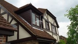 Rosewood fascia with rosewood tongue and groove soffit, half round brown guttering and rosewood cladding